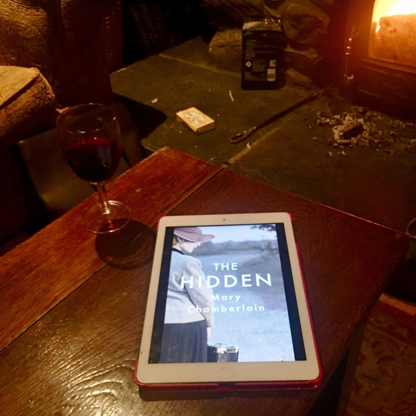 My ecopy of The Hidden in front of a wood burner with a glass of wine.